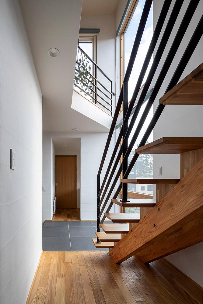 透かし階段が2階LDKに家族を導く。奥のほうには、洗面スペースをはじめとした水まわりが集約されている