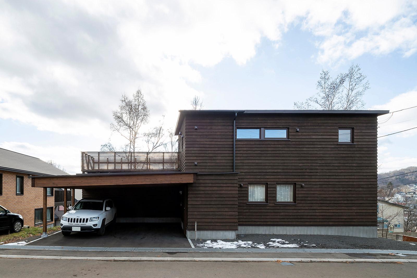道南スギ板張りの外観は、奥さんが希望した自然の中に建つ木の家そのもの。屋根付きのアプローチが除雪作業の負担を軽くしてくれる