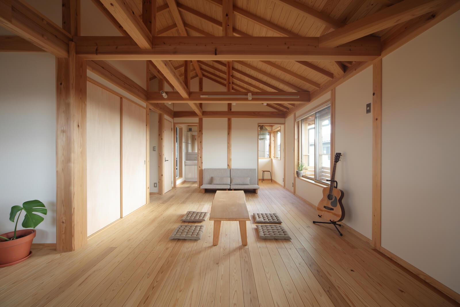 小屋組みを現しにした天井に職人技が宿る20帖の2階居室は、間仕切りで3室に分割可。子どもが小さいうちは広い空間でのびのびと、大きくなったら個室に、といった使い方も。梁の部分に床を設けてロフトスペースをつくることもできる
