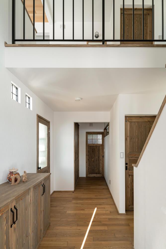 施工途中で吹き抜けの腰壁をアイアンの手すりに変更し、造作仕様のシューズボックスも高さを抑えることで、明るさと広がり感がアップした玄関ホール
