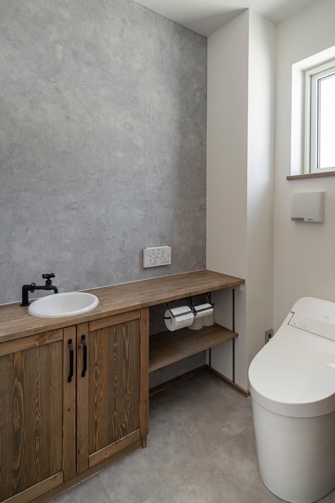 黒をアクセントに用いた造作手洗いカウンターを設けた1階トイレ
