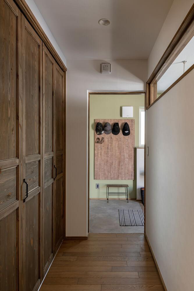 玄関ホールと農家玄関は、採光窓と造作収納を設けた廊下でつながっている