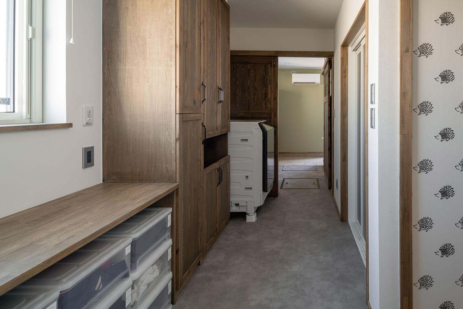 農家玄関からも動線がつながるユーティリティは、昇降式の物干し、造作の家事カウンターや収納棚を備える