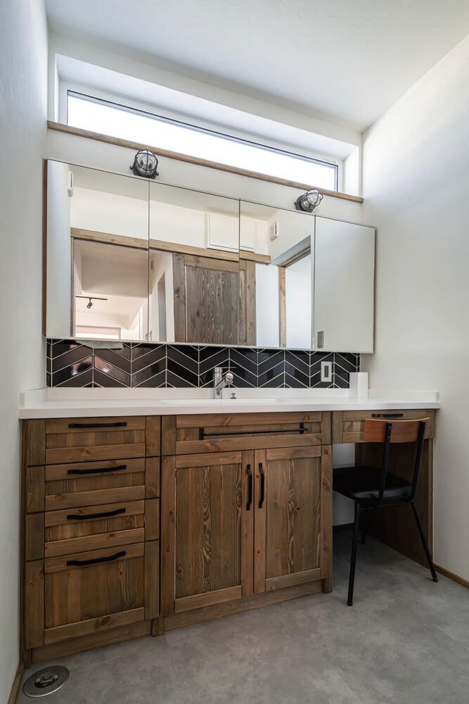 タイルやマリンランプを採用した洗面台には、奥さんの化粧スペースも設えられている。採光窓も設けられ明るい雰囲気