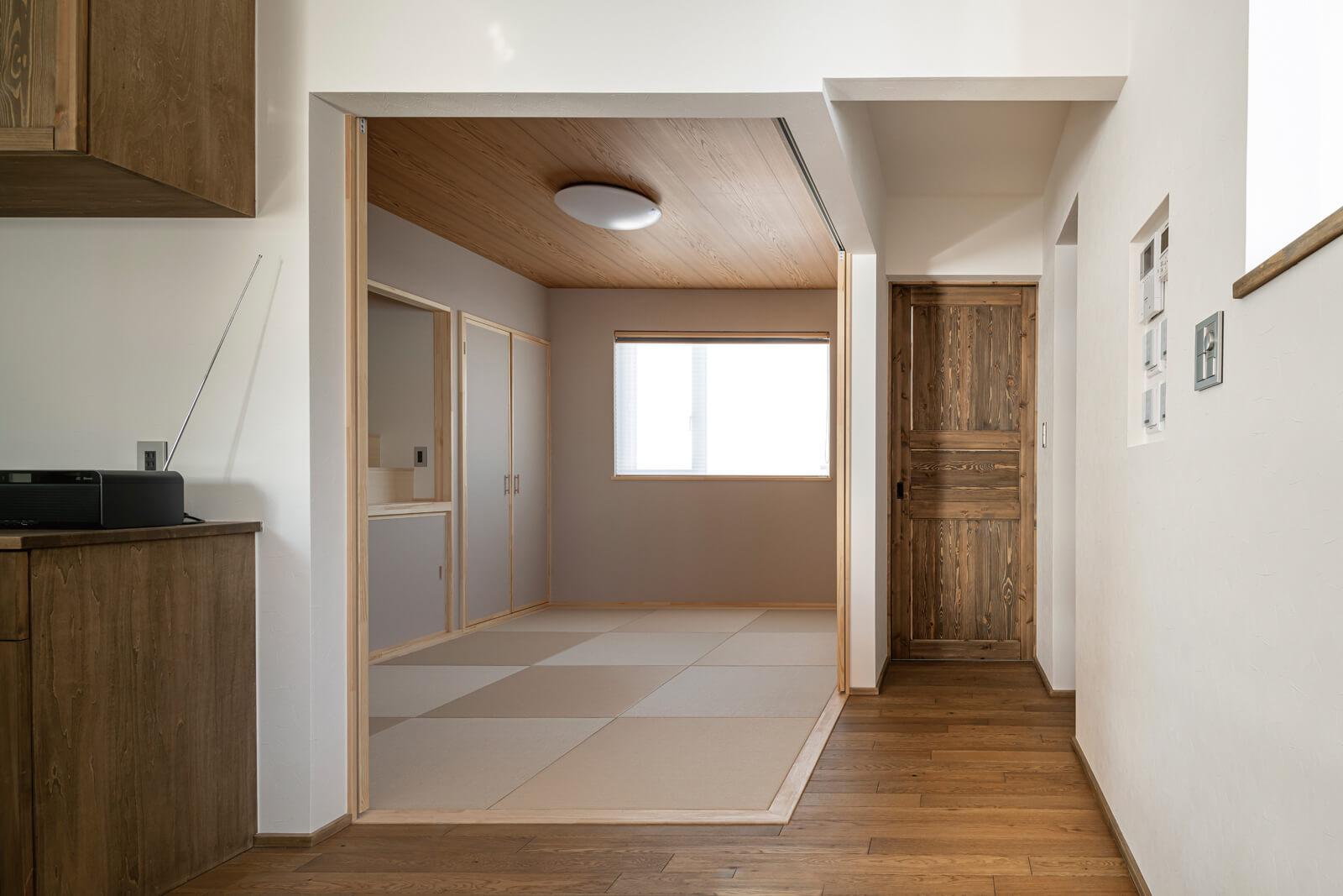 琉球畳を採用し、すっきりとシンプルに仕上げた和室は、開け放していてもリビング・ダイニングに違和感なく溶け込む。来客時には、造作障子を閉めて独立した空間にできる