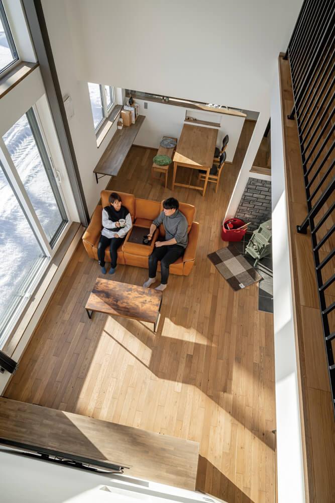 2階の階段ホールからリビングを見下ろす。大らかな吹き抜けが、住まいの1階と2階を緩やかにつないでいる