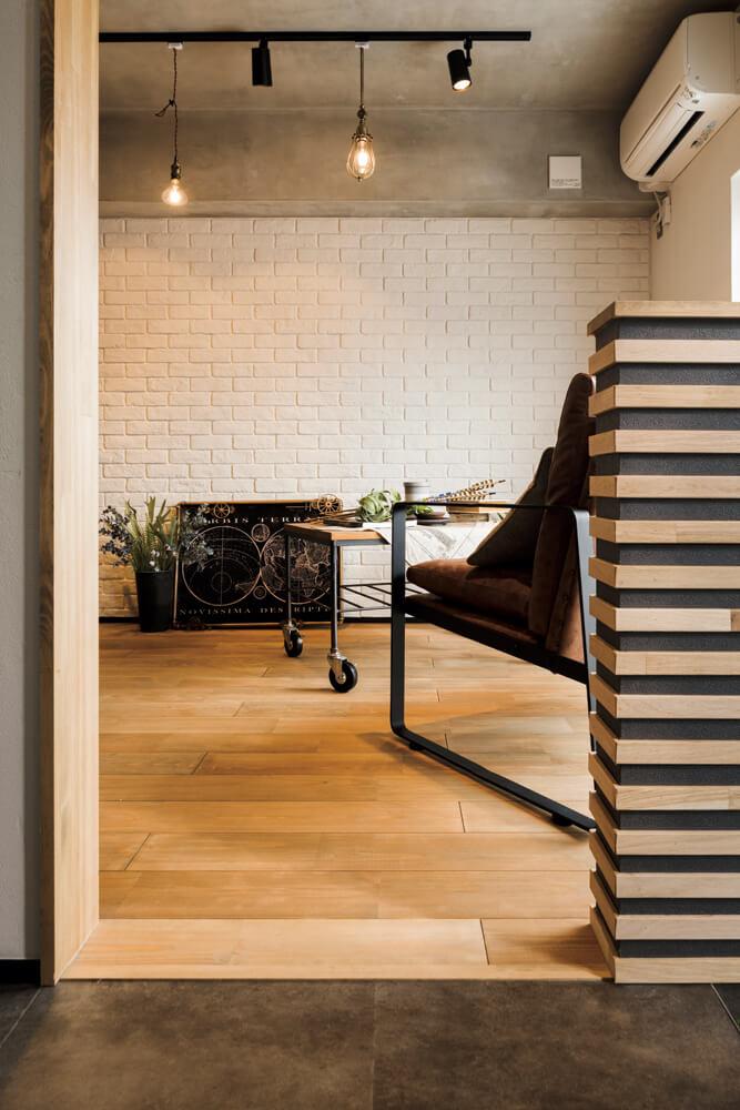 玄関から見たリビング。木材、アイアン、モルタル、レンガなどを絶妙に組み合わせ、重厚になりすぎないインダストリアルデザインにまとめている