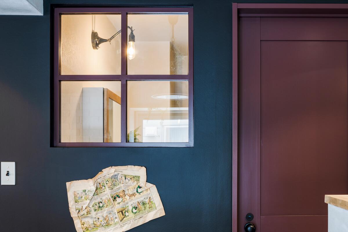 LDKとユーティリティの間に内窓を設け、広がりのある空間を演出。窓枠とドアのボルドーカラーが映える