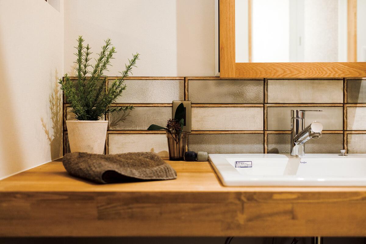 ウッドフレームのミラーやガラス製のタイルなどを使用した洗面化粧台