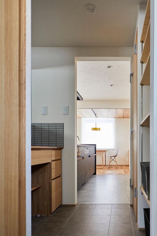 ユーティリティからキッチンへ延びる動線に、洗面スペースと食品庫、ボイラー室を兼ねた空間が設けられている