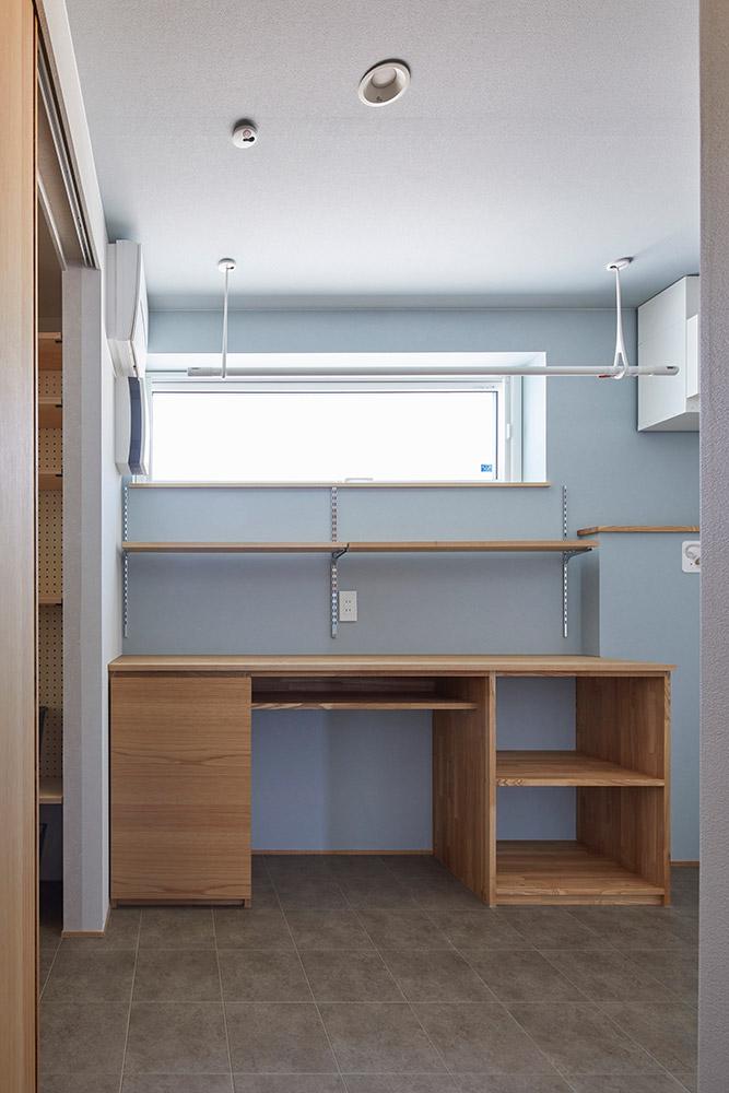 スペースを広めに取ったユーティリティは、乾いた洗濯物を畳んだり、アイロンがけに便利なカウンター付き収納棚を備える