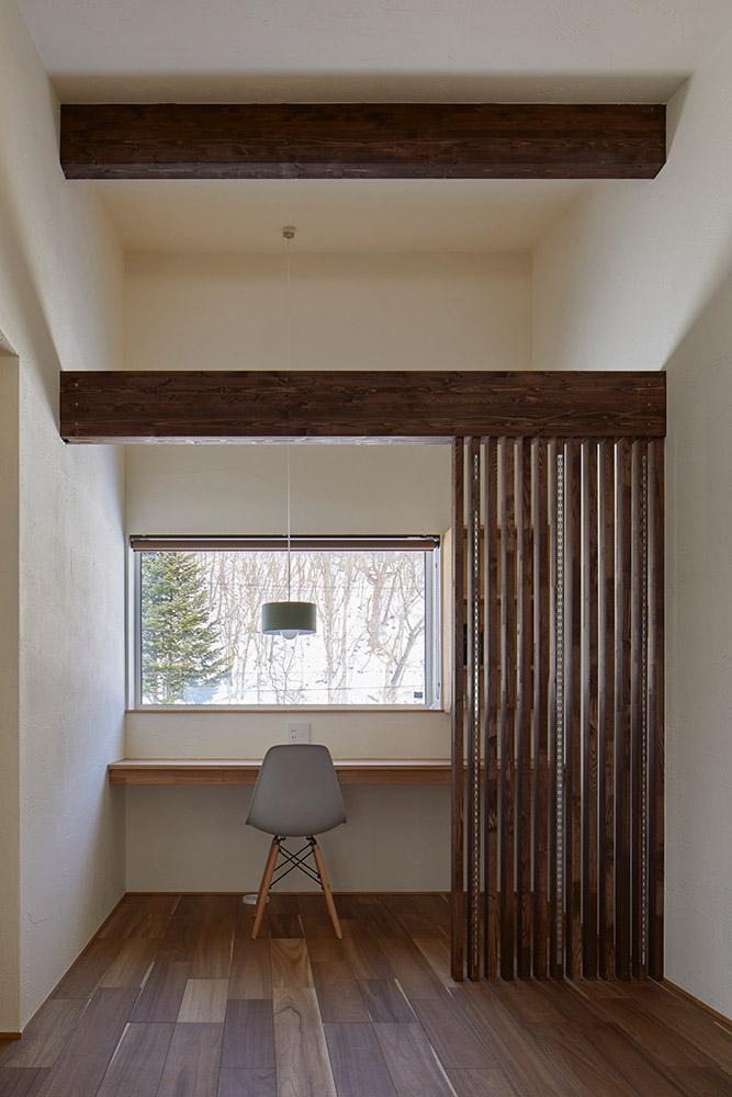 2階寝室の横には、眺めの良いワークスペースがある。本棚付きのカウンターは造作。間仕切りのルーバーには、棚板金具を取り付けてある