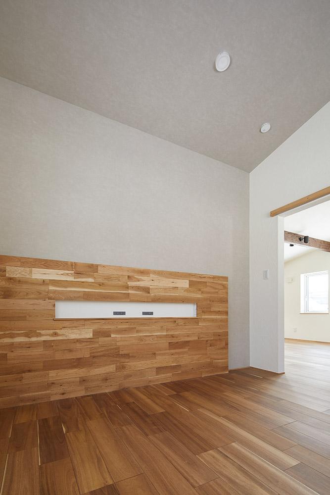 コンパクトにまとめた寝室。壁にフローリング材を張り、コンセント付きのヘッドボードを設えた