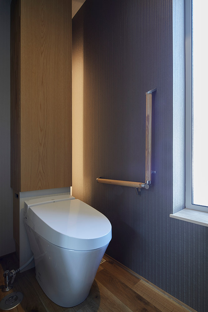 空間をコンパクトにまとめたトイレには、間接照明を設えて奥行き感を演出。タンクレストイレの背後は造作収納