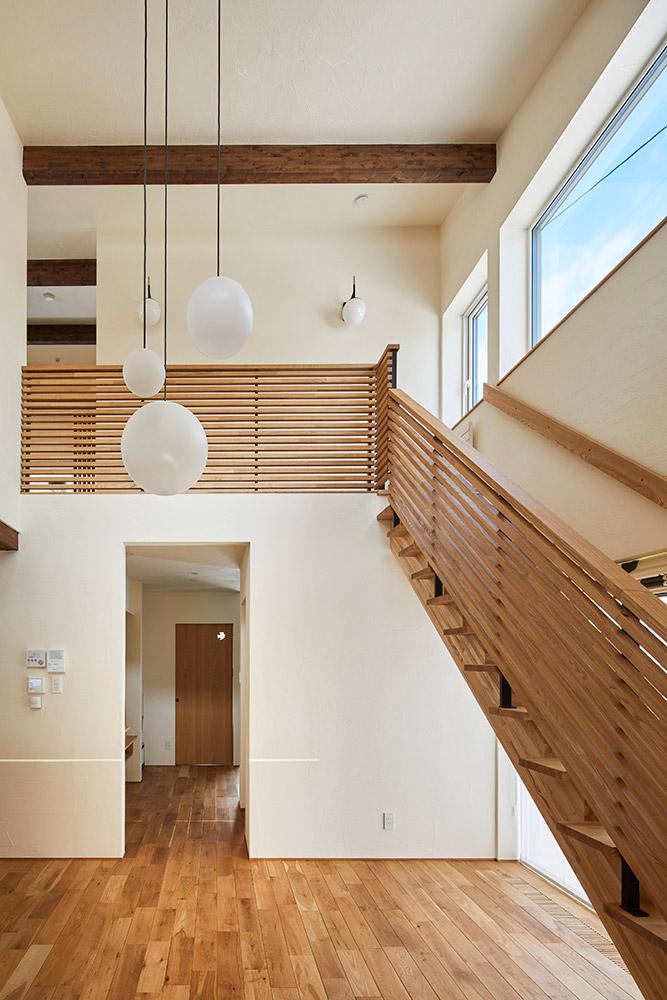 屋根なりの天井まで延びる吹き抜けが、10帖のリビングに心地よい広がり感を与える。アイアンとタモを組み合わせたルーバー状の手すりが、おおらかな空間のアクセントに