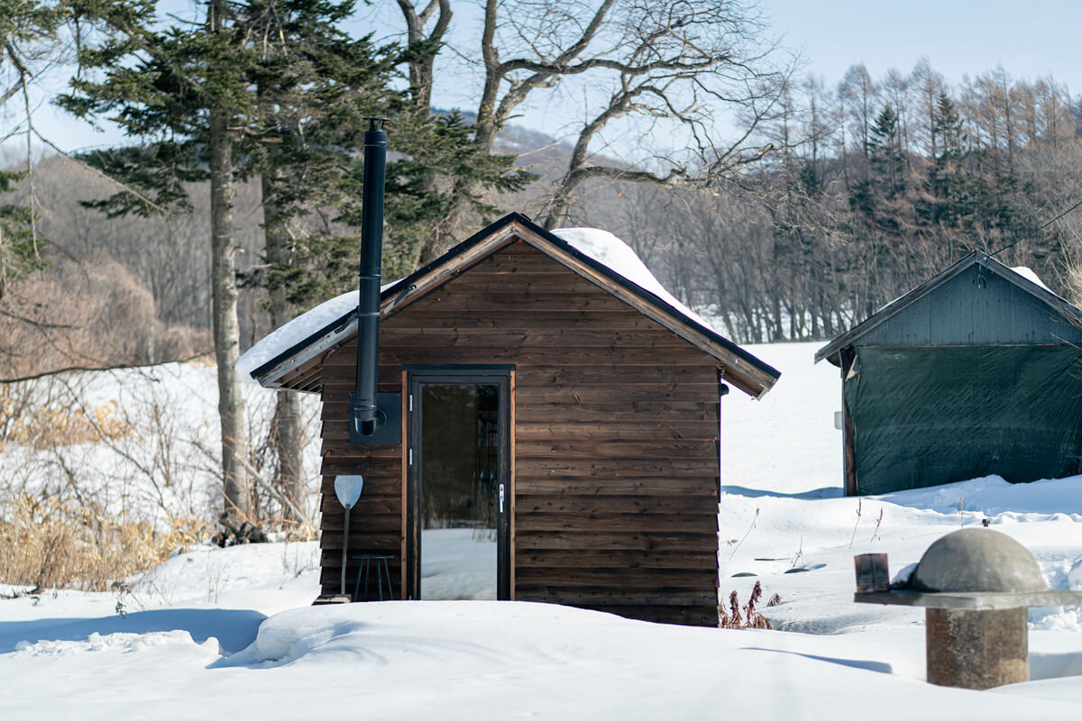 小屋の屋根の形状は、もともと敷地内に建っていた三角屋根の車庫(写真右奥)に合わせてデザイン。出入り口のドアは、全面ガラスで窓のような機能も兼ねる