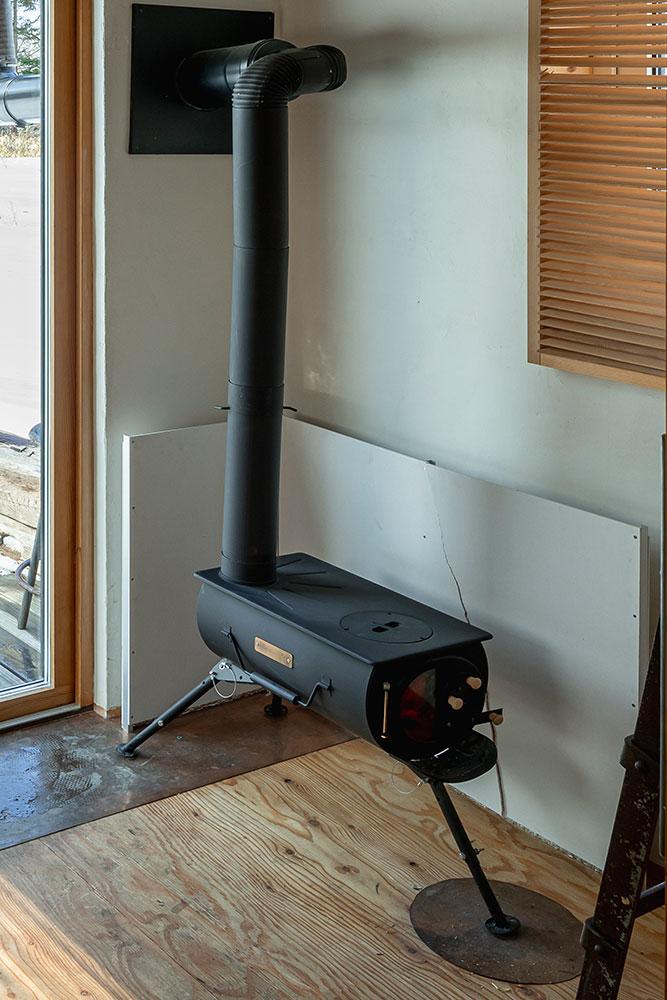 「この小屋の暖房としては十分」というアウトドア用の薪ストーブ。炉壁は一部がひび割れてしまっているものの、自作で簡単な構造のため、スレート板を取り替えればよく、経済的でもある