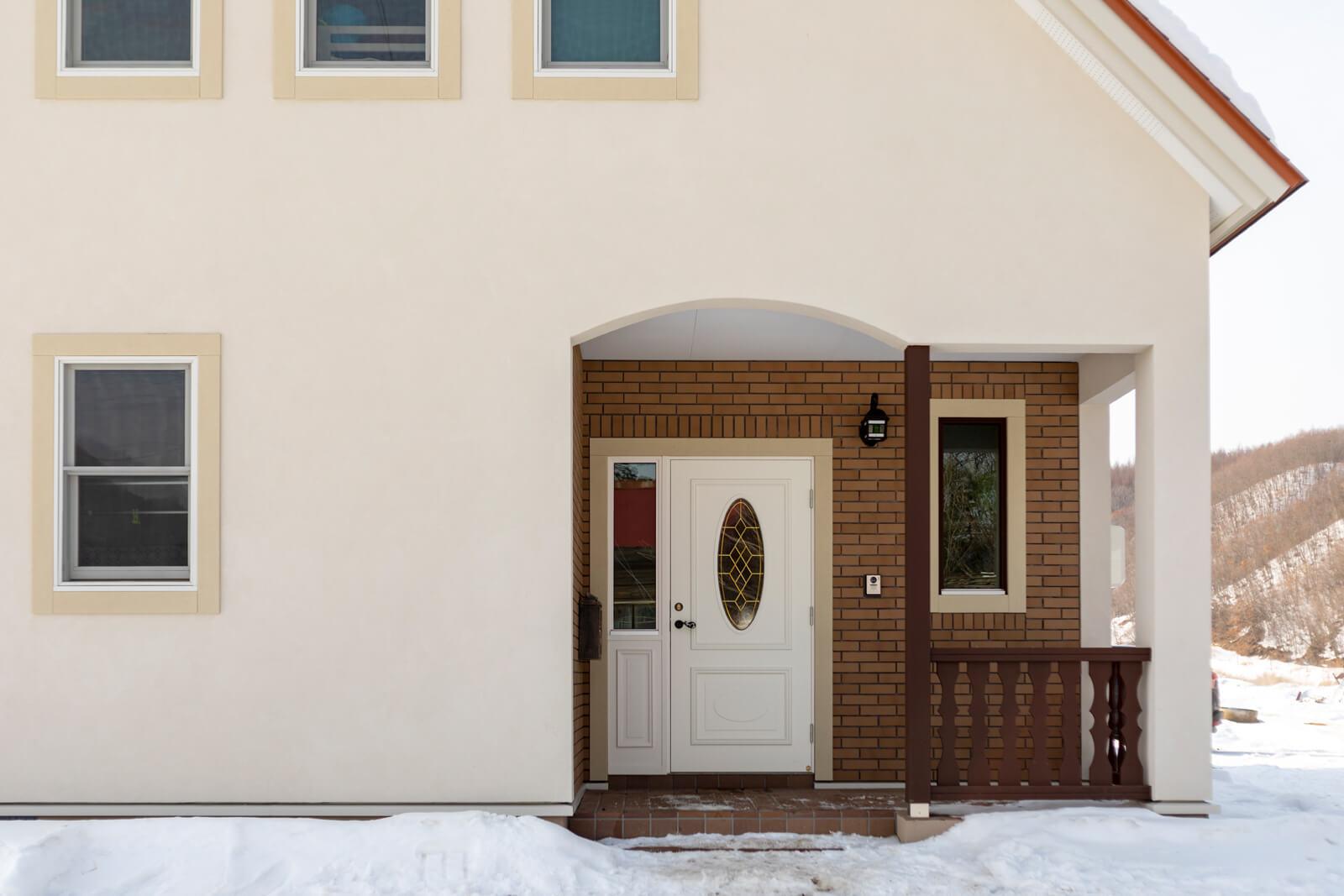 広々とした玄関アプローチ。タイル張りの壁に白い玄関ドアが映える