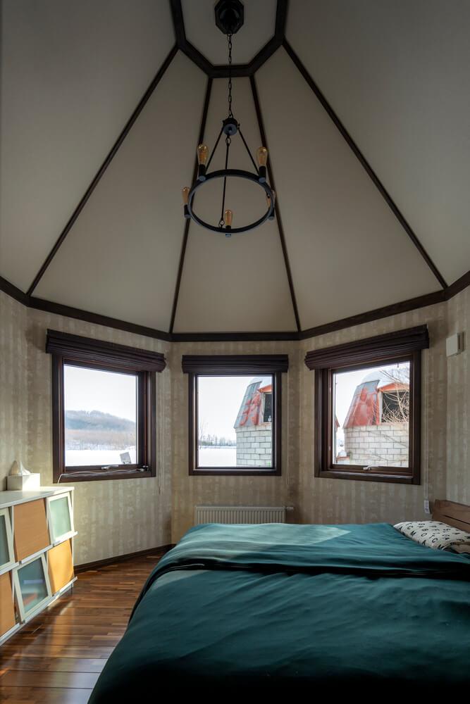 ウォールナットの上品さが漂うご夫妻の寝室は、塔の形に合わせて設えられた3つの窓が印象的