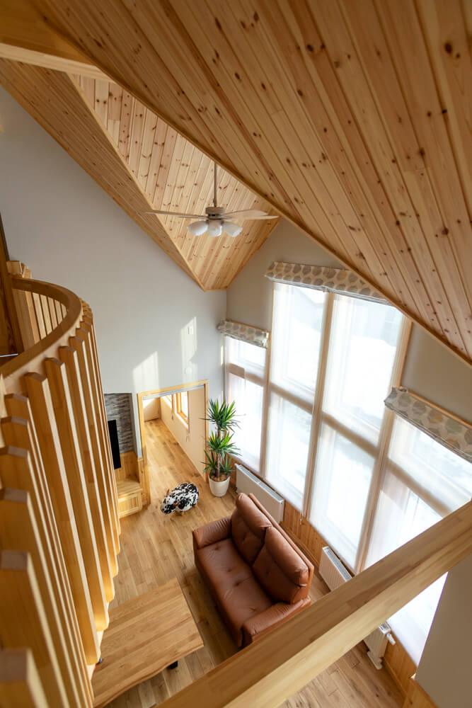 吹き抜けからリビングを見下ろす。2階多目的ホールのアールの柵や鋭角の天井が空間にメリハリを与える