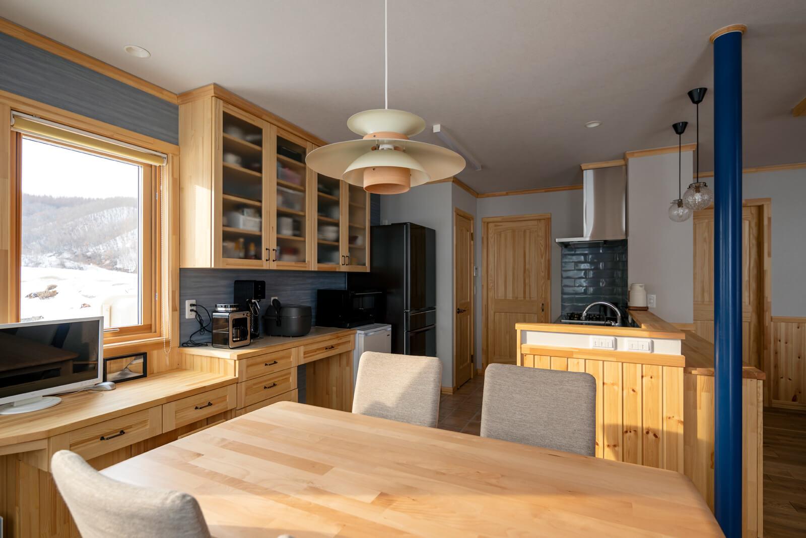 造作背面収納のおかげでスッキリとしたキッチン。奥のドアは農家玄関につながる。この動線のおかげで作業から帰ってきて最短ルートで料理ができる