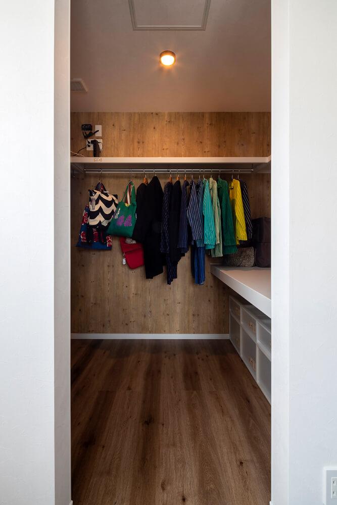 寝室には広いウォークインクローゼットを併設。家族の衣類がたっぷりと入るゆとりの設計。壁は木目調クロスを張って仕上げた