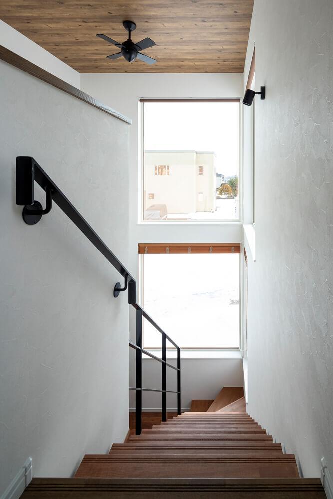 木と白い壁と手すりのアイアンのコントラストがシンプルで美しい階段まわり。2つの大きな窓を通して、まっすぐに視線が抜けて気持ちがいい