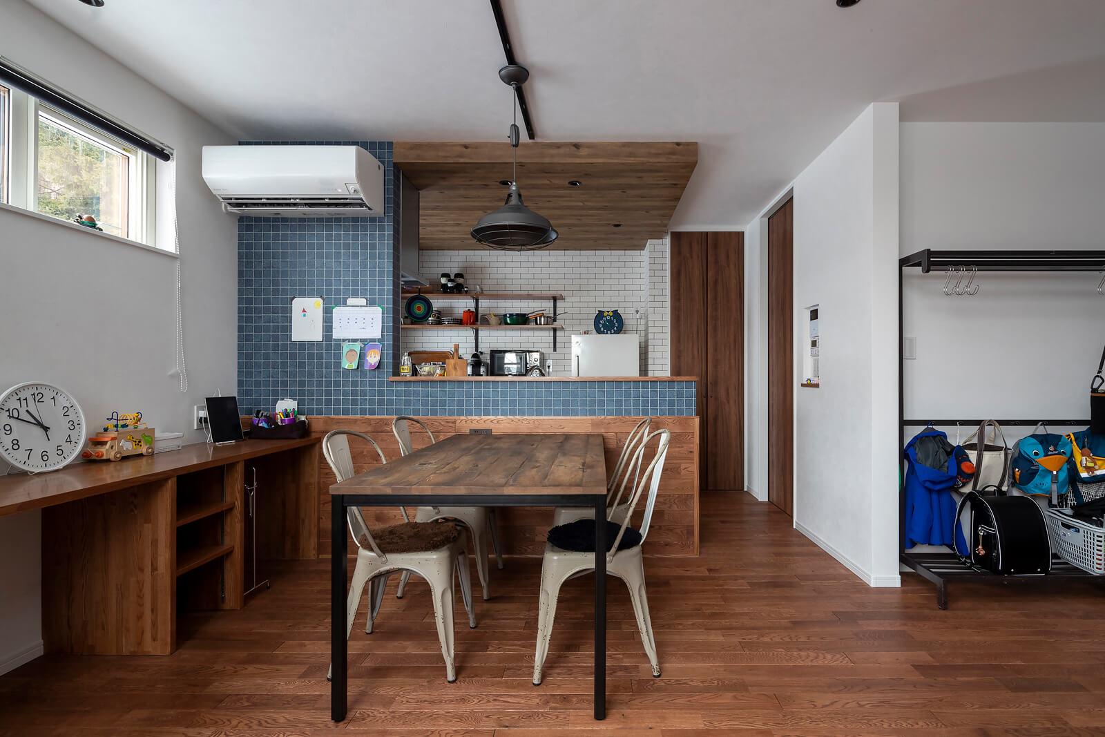 青いタイルや木の風合いがやさしい印象のキッチンのイメージは、北欧スタイルのカフェ。ダイニングもインダストリアルテイスト