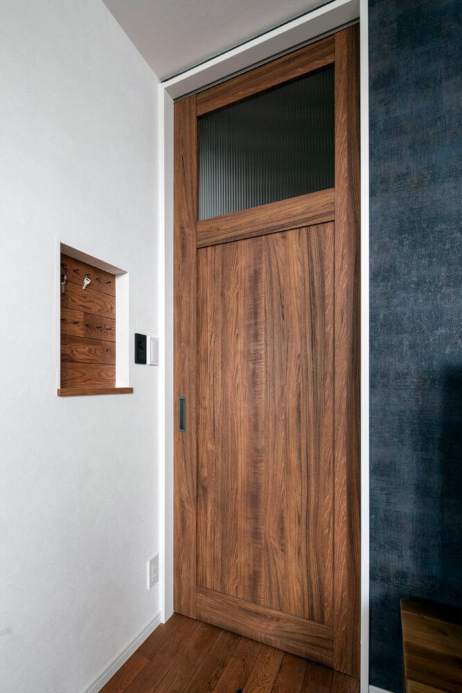 玄関とリビングの仕切り扉は、天井までのハイドア。リビング側の壁に造作したニッチは便利な鍵置き場に
