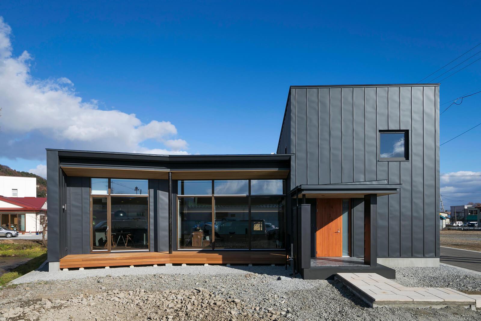 すっきりとした縦平葺きの黒ガルバリウムと大開口が特徴的外観デザイン。南面の連続サッシは、壁をすべて取り払ったかのような圧倒的な開放感