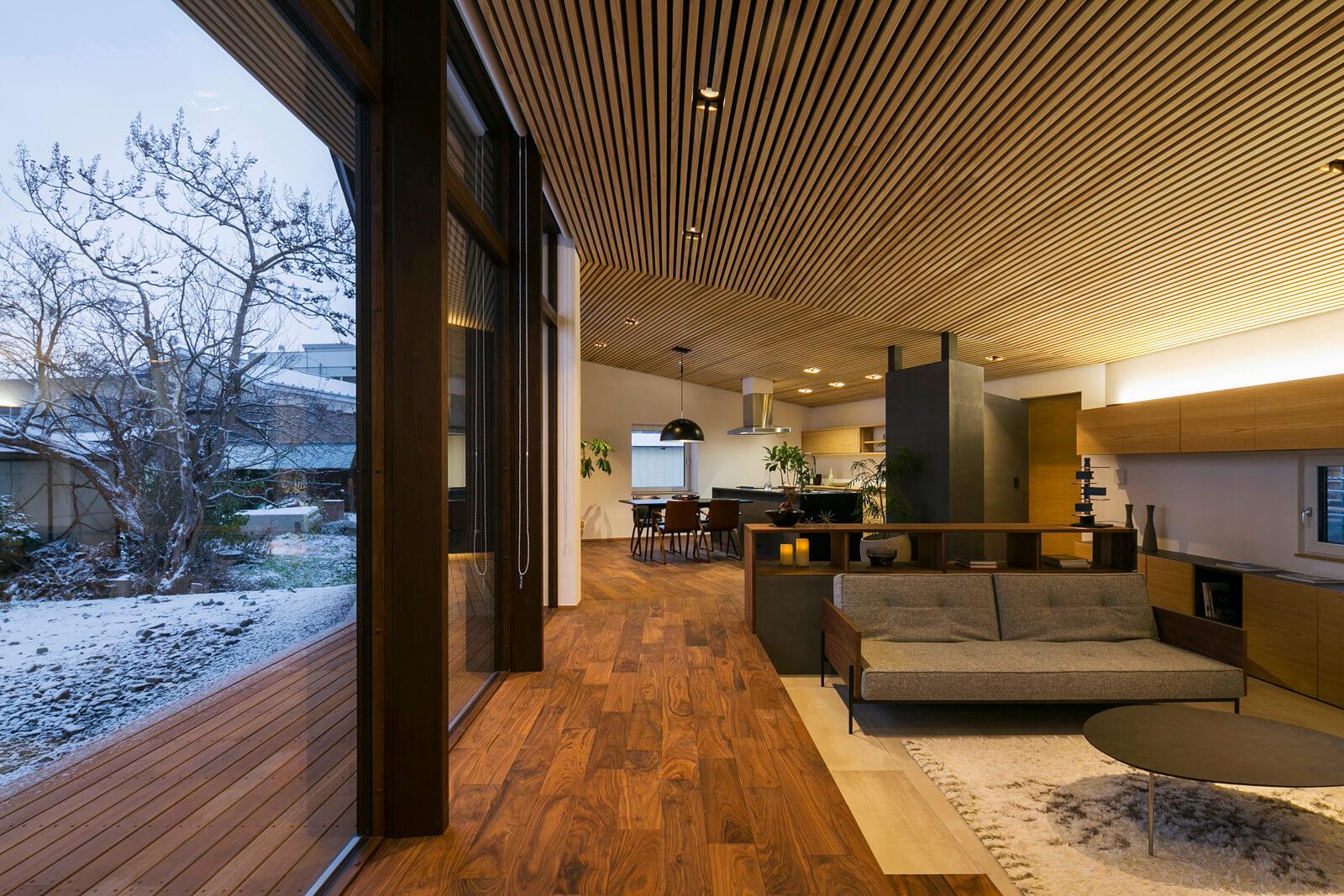 連続する木製サッシのトリプルガラスが室内奥深くまで陽射しを取り込む