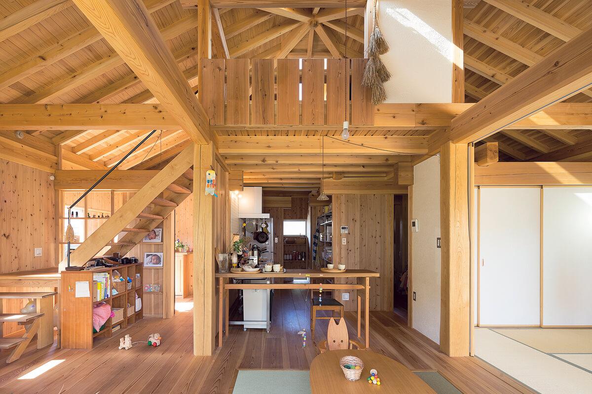 リビングから北側を見返す。キッチンがこの住まいの中心になっていて、そこに立てば家全体がほぼ見渡せ上部の個室の気配も感じられる。木の温もりにあふれた空間