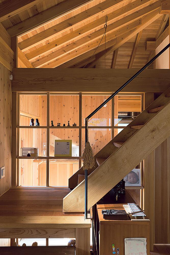 アトリエと玄関の間にはガラスの壁が。絵本や写真を飾り、この家らしい間仕切りになっている