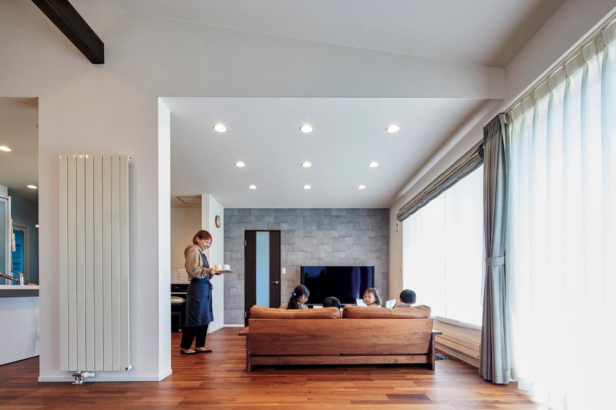 連続する大きな窓が室内を明るく。白を基調としているリビング空間にテレビボード裏のアクセントウォールが空間を引き締めている