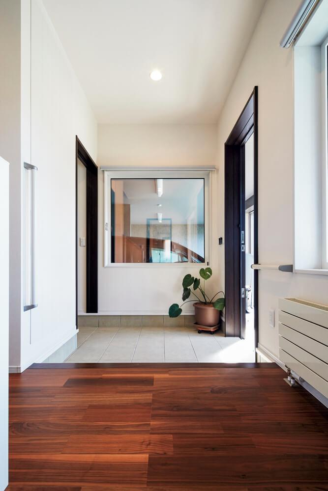 玄関ホールからガレージ方向。玄関壁には「エコカラット」を採用。消臭などの機能とともにアクセント的効果も