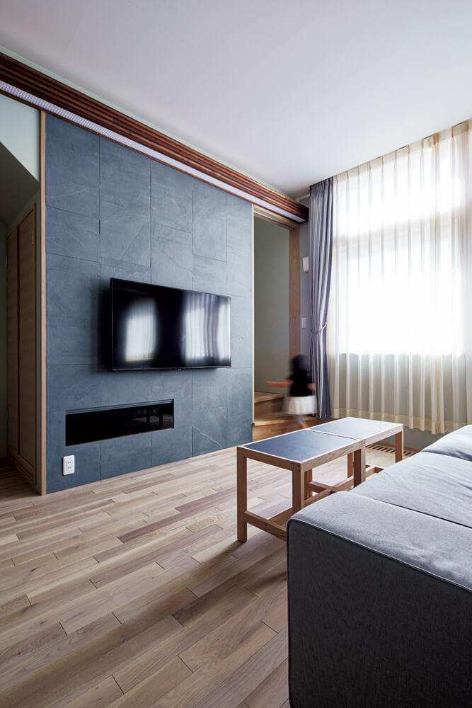 テレビ背面の壁は、マットグレー系の石材をセレクト。機器を収納する扉はブラックガラスで制作した