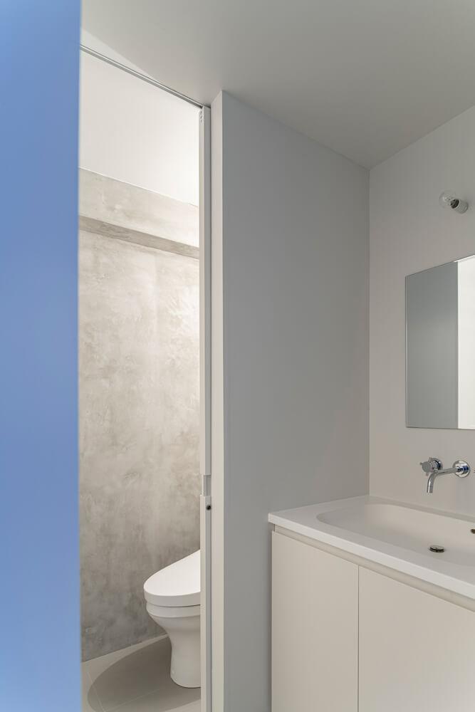 洗面スペースは塗り壁、トイレはコンクリートと素材の変化が楽しい
