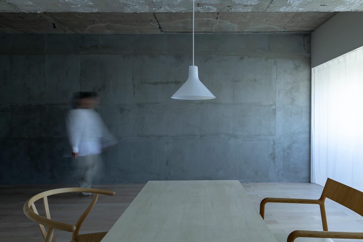 ダイニングテーブルに腰をかけ、ふと視線を移すと目の前には無機質なコンクリートの壁