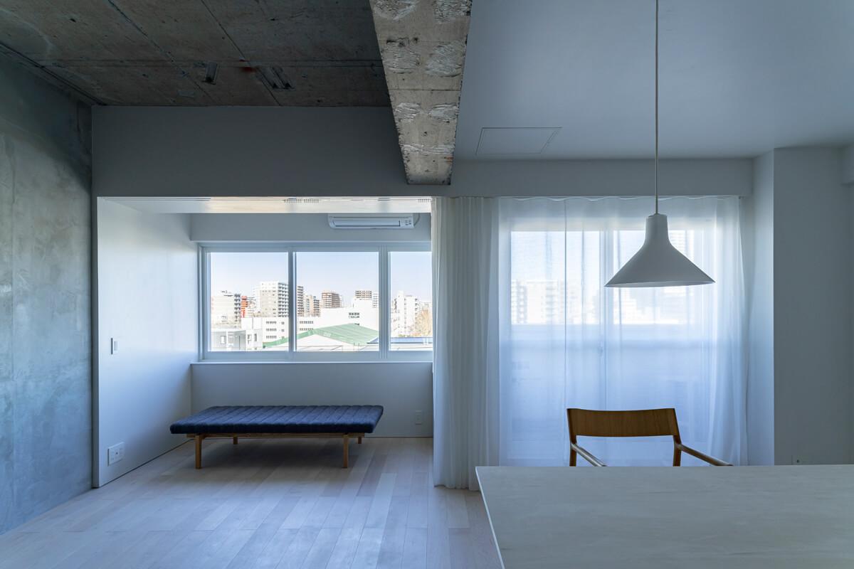 隣り合う異なる素材の境界線のように真っ直ぐに延びる長い梁。写真左手のコンクリートの空間は、天井も現しに