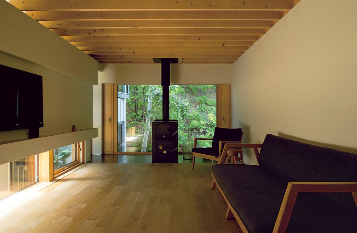 敷地の裏に迫る森を大胆に切り取ったピクチャーウィンドウ が印象的なリビング。室内の明るさがほどよく抑えられ、裏山 の緑がより映える。通風は窓の左右の開口からとることがで きる