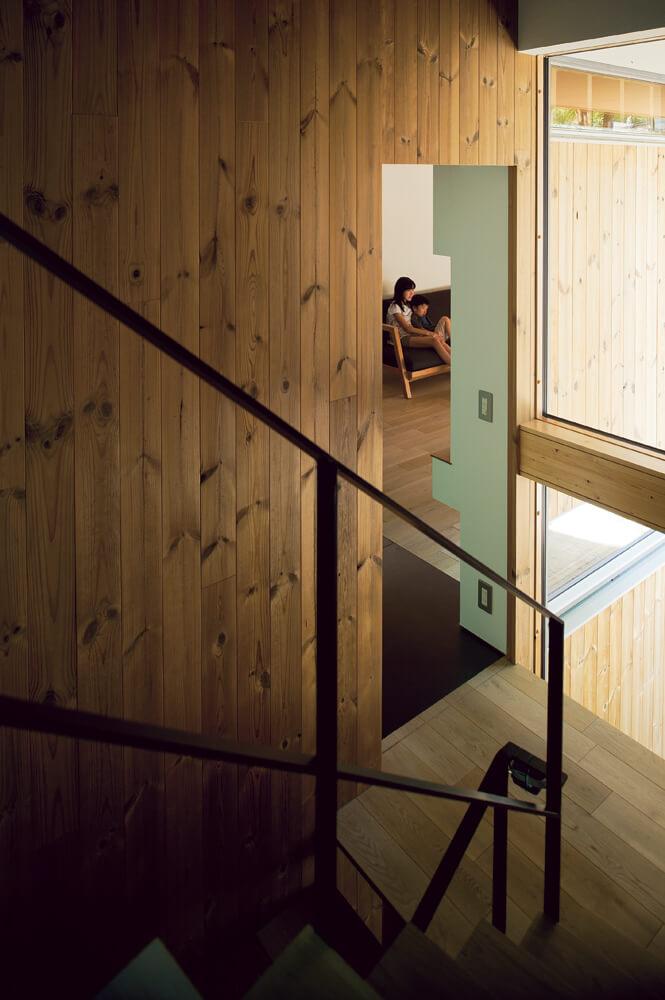 ダイニングから階段室越しにリビングを見る。窓ガラスで囲わ れた階段室の壁材と外壁材は素材を統一し、内と外の境界を 曖昧にして空間を連続させている