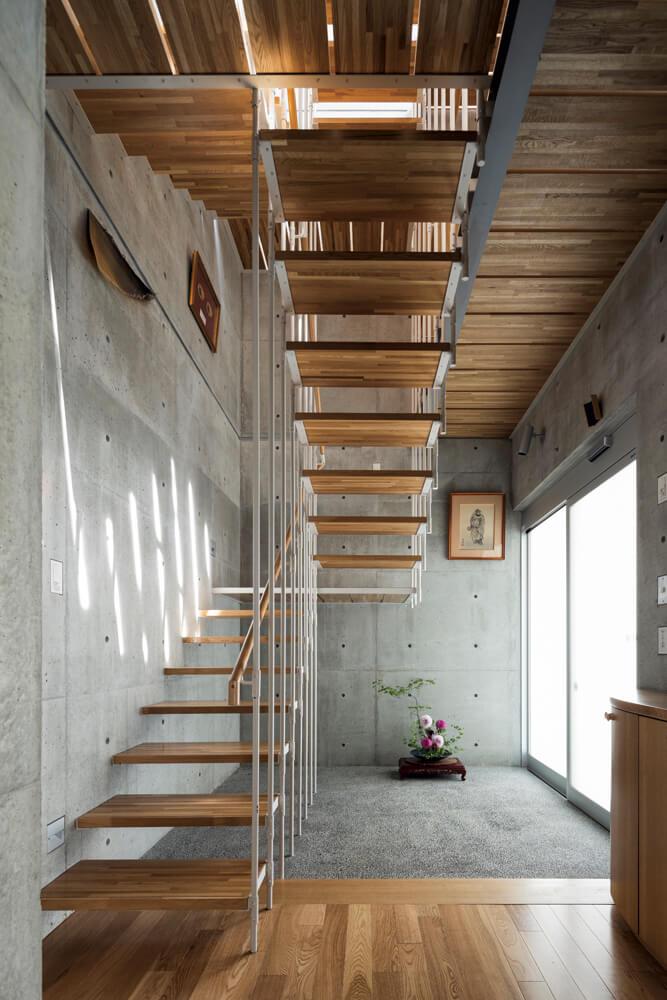 1階の通路に沿って設けた住居用の玄関。家の中央に配した階段室はもう1つの縦 の抜けとして、3階までつながって空気の流れをつくり、すのこ状の廊下や踊り場が 光と風を屋内に行き渡らせる