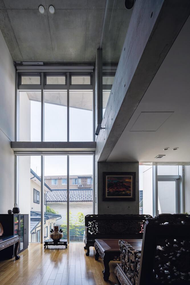 吹き抜けいっぱいに設けた大迫力のカーテンウォールで、応接室兼リビングは明るく 伸びやかな空間に。内部のRC壁は蓄熱層としても働くよう、素地仕上げとしている。 吹き抜け最上部の外倒し窓が重力換気を促し、室内に外気を呼び込む