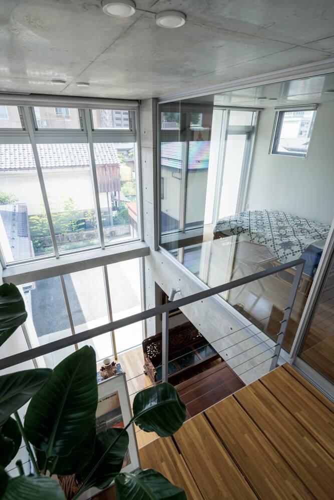 3階の吹き抜けに面した部屋は、娘さんご夫妻の寝室。ガラス窓を介して空間 が緩やかにつながる。プライバシーは縦型ブラインドで確保 中:鉄筋の支持材と木の踏板で構成された軽やかなデザインの透かし階段。3階 から射し込む光が、コンクリート壁に美しい陰影を描く