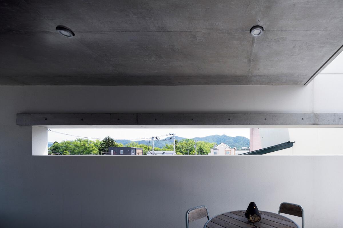 テラスの壁に設けた横長のスリットは、絶 妙な位置で近くの杜や遠くの山並みを切り取る