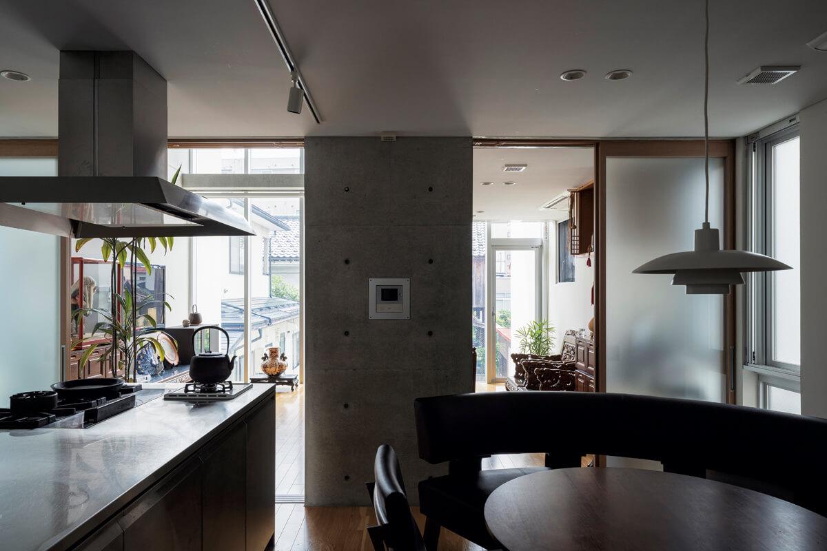 応接室兼リビングの隣に配したダイニング・キッチンは、ご家族の団らんの場。 オールステンレス製の特注アイランドキッチンには、旧宅時代から愛着を持って使 ってきた鋳物製の五徳付き業務用コンロを組み込んだ