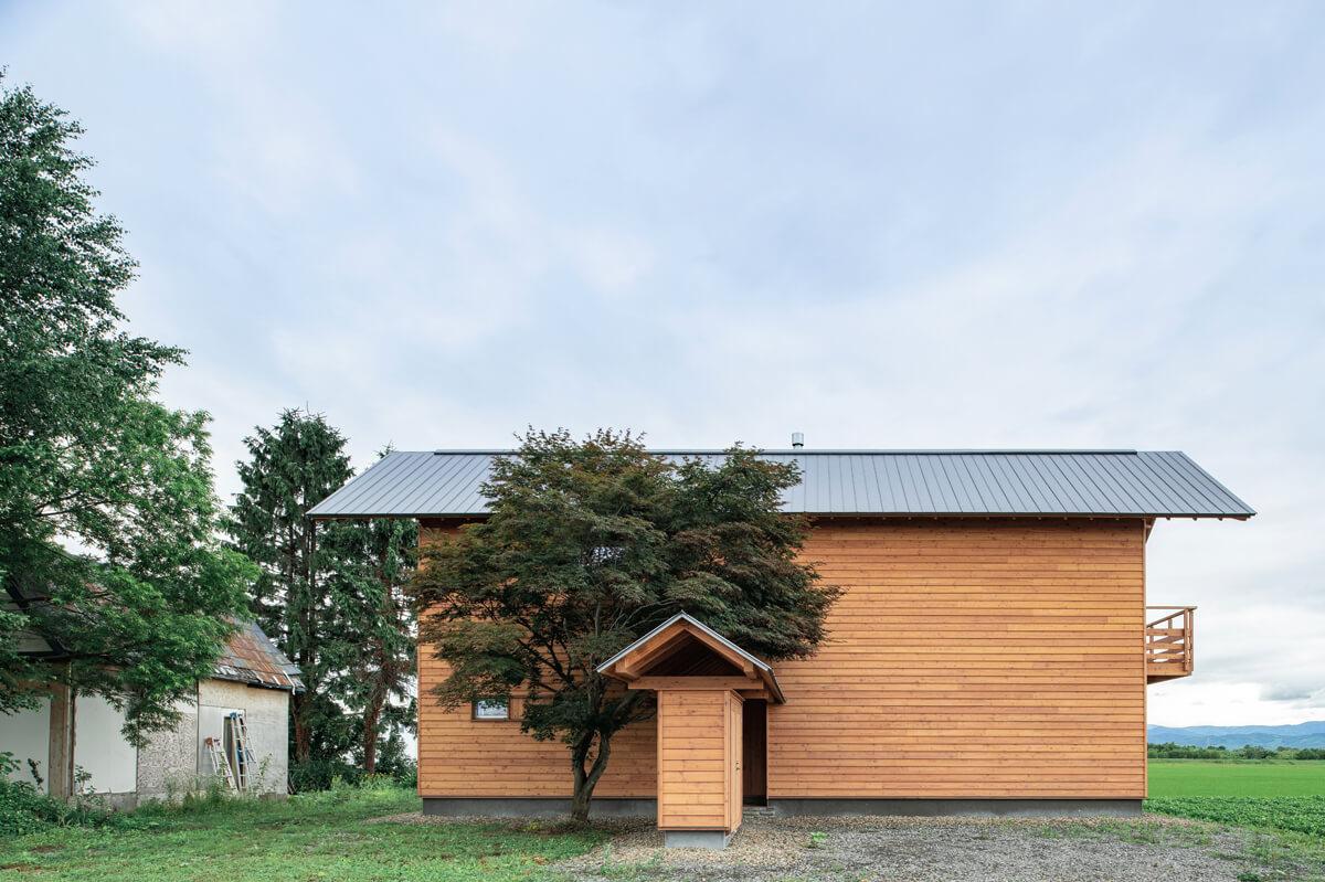 建物は総2階建て。8間×2.5間とコンパクトにすることで表面積を減らし、冬期の 熱損失を軽減している。玄関ポーチに覆いかぶさるように葉を茂らせている木はカエデ。 もともと敷地内に生えていたこの木の存在を考慮して家の配置を決めたという