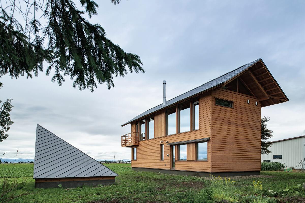 :田園風景を望む方向に大きく開いたOさんのお住まい。外壁は道産カラマツ材仕 上げ。屋根は木造折板構造で、断熱層と構造を一体化させたモノコック状の断熱屋根 としている。庭の一角には、家族でアウトドアを楽しむための「あずまや」も設けた