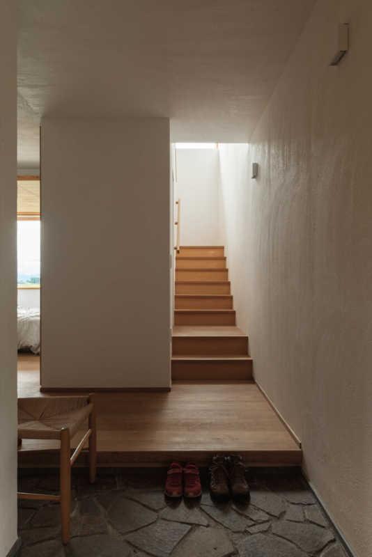 玄関に入るとすぐ目の前に階段。壁・天井は道産ホタテ漆喰塗り、玄関の三和土 には北見産の鉄平石を用いるなど、道産の素材にこだわっている