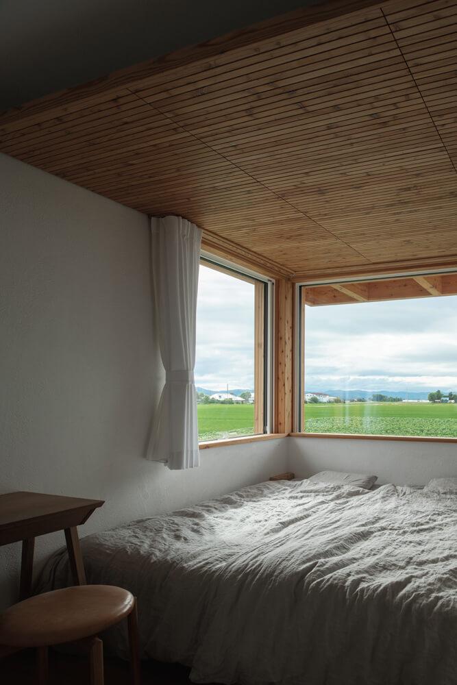 木天井が心地よい寝室からも美しい田園風景を望むことができる。2階テラス の浮遊感は、この部屋からの眺望を遮らないようにするための工夫